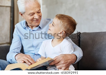 Cute energetic kid enjoying time with grandpa