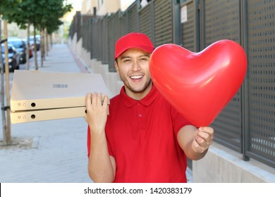 Cute ethnic pizza delivery guy holding heart shaped balloon