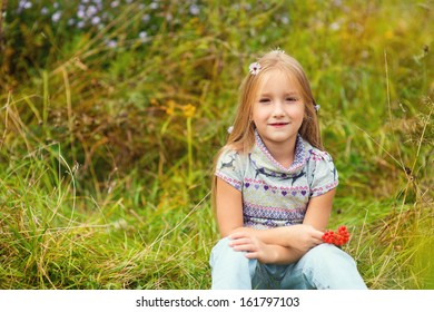 Cute european blond girl sitting on grass with flowers in hair with ash berries in hands
