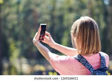 Cute European blondie woman with backpack is taking selfie on her smartphone. Back view.