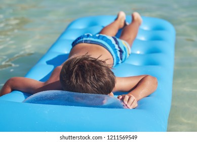 Cute European boy is enjoying his summer vacations on the seaside. He is laying on the blue inflatable floater.