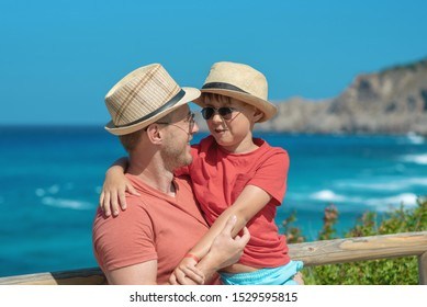 Cute European boy is on his father's hands in front of picturesque wavy sea, enjoying summer holidays. They wearing similar clothes sun hats and sunglasses smiling and looking to each other.
