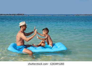 Cute European boy is sitting on a blue floater with his dad. They are happy, smiling and having fun.