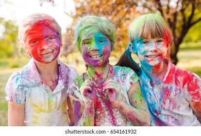 cute european child girls celebrate Indian holi festival with co