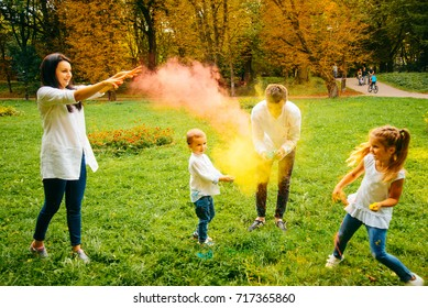 cute european family plaing with holi paints in the park in summer day