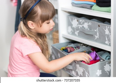 Cute European little girl with blond hair brings wardrobe order, puts everything in its place hides things in boxes
