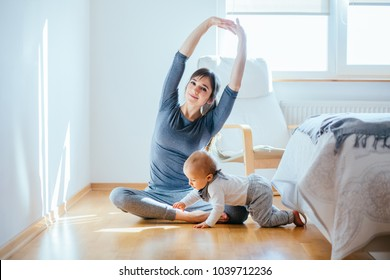 Cute european mother doing yoga or pilates while her infant baby boy playing near at cozy simple home interior. Motherhood, healthy lifestyle and people concept.