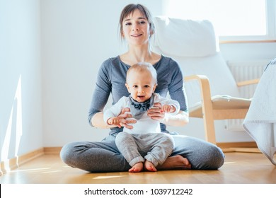 Cute european sporty mother playing with cute infant baby boy. Little son sitting with his mother on the floor at cozy simple home interior. Motherhood, healthy lifestyle and people concept.