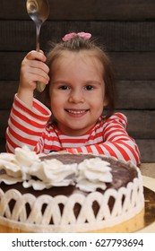Cute excited smiling little girl with spoon in hand going to eat chocolate cake. The joys of childhood. Celebration party.