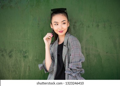 Cute exited Asian girl thinking and smiling near green wall looking to the side