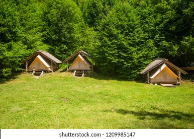 Cute fabric tents protected by wooden huts in alpine environment in Adrenaline Check eco camp, Slovenia.