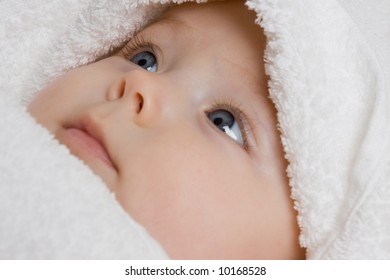 A cute face of a baby covered with soft, white towel.
