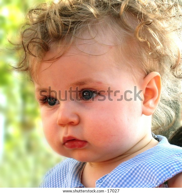cute face of baby with curly hair and blue eyes and a serious expression in an outdoor setting