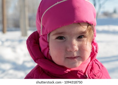 cute face of a little girl in winter clothes on the street