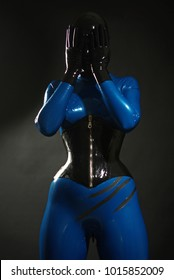 cute faceless kinky girl wearing blue latex catsuit and black rubber corset posing in the dark studio on black background alone