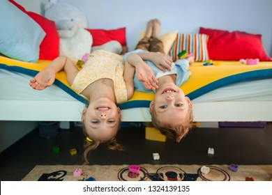 cute, fair-haired funny laughing children of 7-8 years old play on a bright multi-colored children's bunk bed and hang down lying upside down