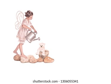 Cute fairy with wings, standing on the rocks, watering his Teddy water from the watering can, so it does not dry up.