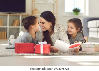 Cute family celebrating Mother's Day at home. Happy young woman lying on floor with her children, reading greeting card, thanking kids for present, touching noses and Eskimo kissing with her daughters - Shutterstock ID 1918076726