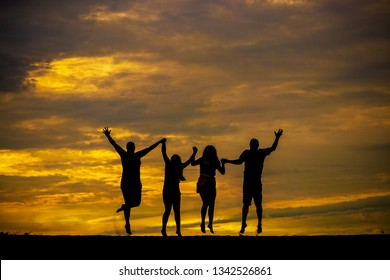 Cute family of four, holding hands, jumping on the sand of a beach, with clouds in a yellow sunset