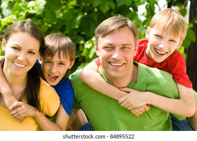 cute family of a four at nature