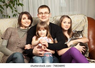 Cute family of four on their sofa at home