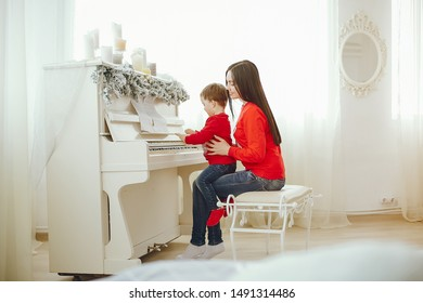 Cute family have fun in decorating room. Beautiful mother with little son. Family in a red sweaters. Little boy play on a piano