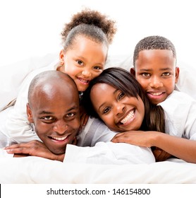 Cute family lying in bed - isolated over a white background