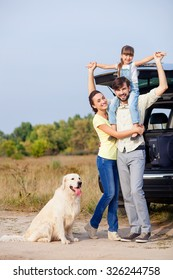 Cute family is resting in the nature and smiling. They are standing near car and dog. The father is holding daughter on shoulders. His wife is embracing him with love