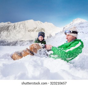 Cute family scene: father and son play with dog during mountain