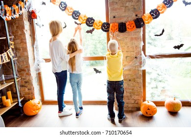Cute family setting the decor for party, mommy with two small blond kids in decorated nice room at home, bricks, wood, loft style, bats, spider nets, carved pumpkins on windows, casual wear