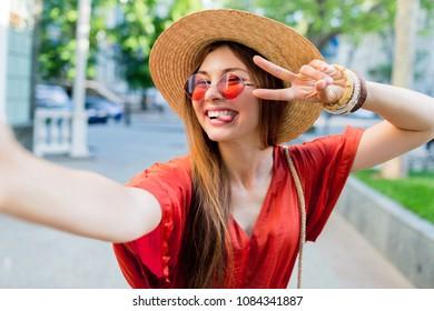 Cute fancy  woman making selfie while walking in  sumner city . Pretty girl having fun , going crazy. trendy  sunglasses .