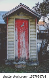 Cute farmhouse outhouse with red door