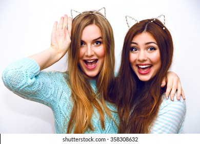 Cute fashion portrait of pretty sisters girls having fun together hugs and going crazy, funny cat ears, mint winter sweaters, white wall, best friends, joy, trend, relations, happy, natural make up.