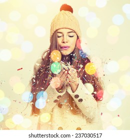 Cute fashionable Caucasian brunette teenage girl blowing confetti. Pretty young woman with beige coat and knitted beanie hat. Square format, instagram filter, string light bokeh.