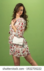 cute fashionable girl on green background with floreal spring dress looking in camera smiling