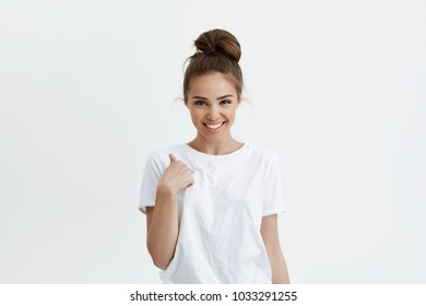 Cute fashionable young european model with bun hairstyle pointing backwards with broad smile and playful expression, standing over white background. Girl shows funny friend who fell asleep on party