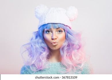 Cute fashionable young woman with pastel purple and pink hair and makeup in fun white knitted beanie hat. Teenage girl with colorful luscious hair pouting and posing. Closeup, studio shot, retouched.