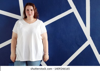 Cute fat girl posing in the studio on the background of a geometric wall. Pretty woman with a magnificent body in blue jeans.