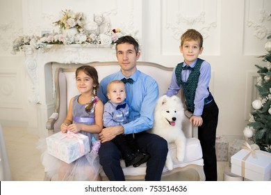 Cute father with three children and Samoyed dog in Christmas decorathion