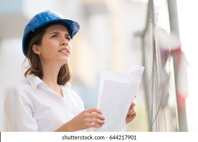 Cute female architect with blue hardhat checking office blueprints looking at something above her among scaffolding on construction site. Selective focus