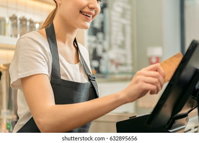 Cute female cashier holding credit card near monitor