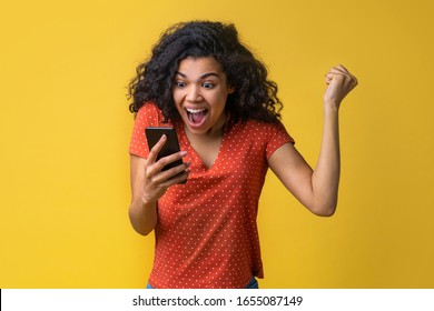 Cute female fan watching football play online broadcast cheering for her favourite team and making winner gesture with her fist being happy about the score. Gambler girl celebrating victory making bet