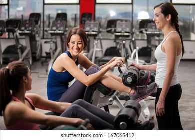 Cute female friends chatting and hanging out in a gym while exercising