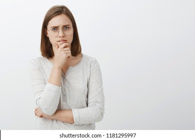 Cute female geek trying solve hard math riddle standing thoughtful over white wall rubbing chin during brainstorm looking at camera while making decision or thinking posing over gray background