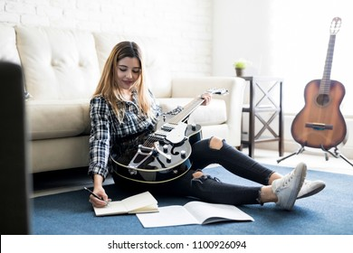 Cute female musician play guitar and writing a new song in her diary