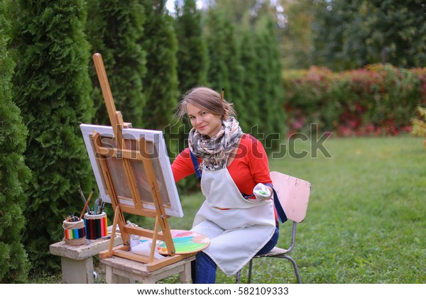 Cute female painter posing, laughing and in front of camera , draws and smiling with brushes and colorful palette in hand, sits on chair near easel in green park outdoor.  Girl with brown hair dresse