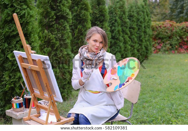 Cute female painter posing, laughing and in front of camera , draws and smiling with brushes and colorful palette in hand, sits on chair near easel in green park outdoor.  Girl with brown hai