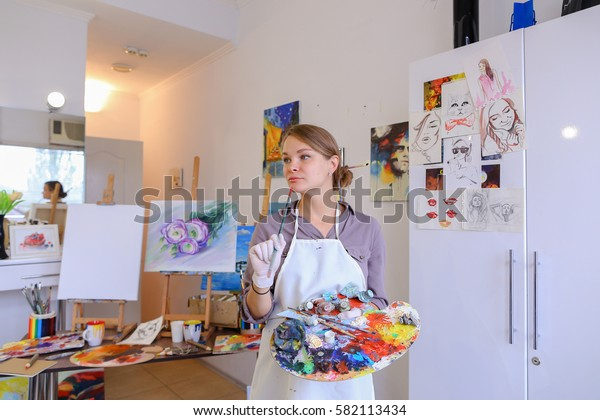 Cute female painter posing, laughing and fooling around in front of camera and smiling with brushes and colorful palette in hand, standing in studio with white art paintings on walls. Girl European