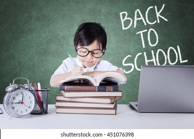 Cute female student studying in the class while writing on the book with text of Back to School