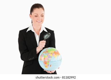 Cute female in suit holding a globe and using a magnifying glass while standing against a white background